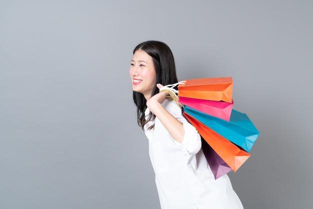 Jovem mulher asiática feliz sorrindo e alegre segurando sacolas de compras em uma camisa branca cinza
