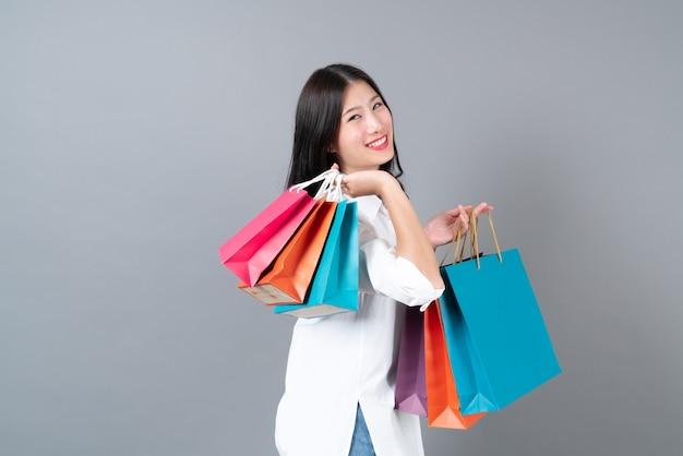 Jovem mulher asiática feliz sorrindo e alegre segurando sacolas de compras em uma camisa branca sobre fundo cinza