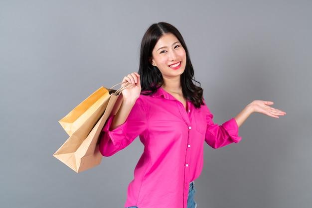 Jovem mulher asiática feliz sorrindo e alegre segurando sacolas de compras em uma camisa rosa cinza