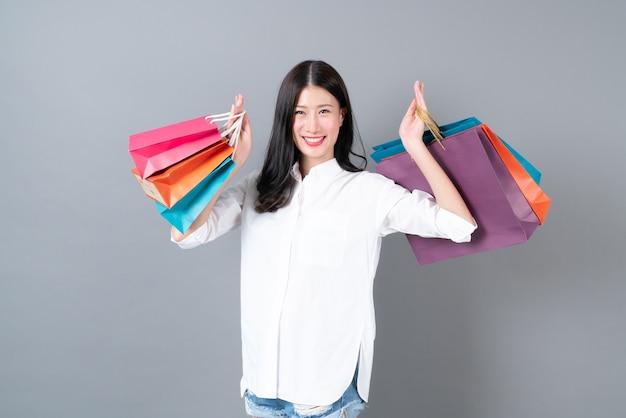 Jovem mulher asiática feliz sorrindo e alegre segurando sacolas de compras na camisa branca