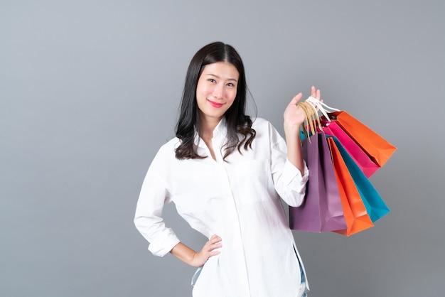 Jovem mulher asiática feliz sorrindo e alegre segurando sacolas de compras