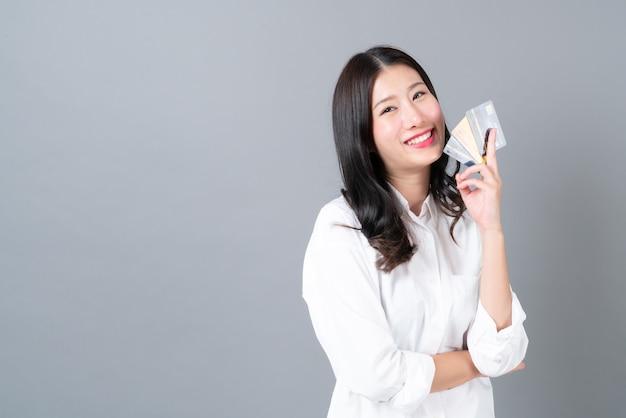 Jovem mulher asiática feliz sorrindo e apresentando cartão de crédito na mão cinza
