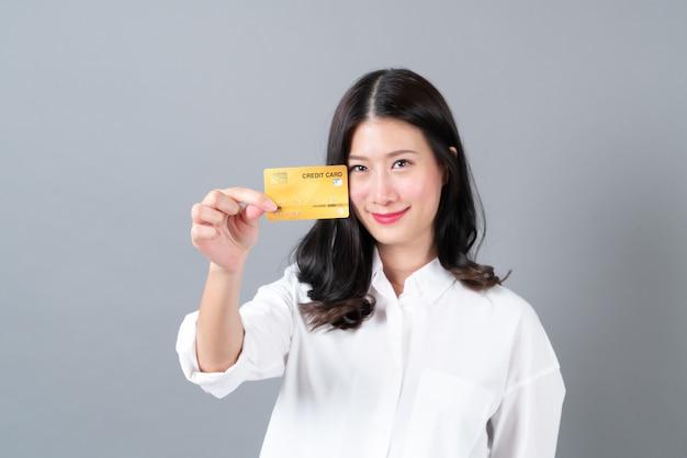 Jovem mulher asiática feliz sorrindo e apresentando cartão de crédito na mão