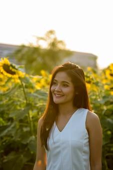 Jovem mulher asiática feliz sorrindo e pensando enquanto olha para o lado