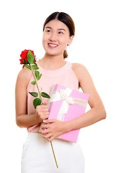 Jovem mulher asiática feliz sorrindo e pensando enquanto segura uma rosa vermelha e uma caixa de presente