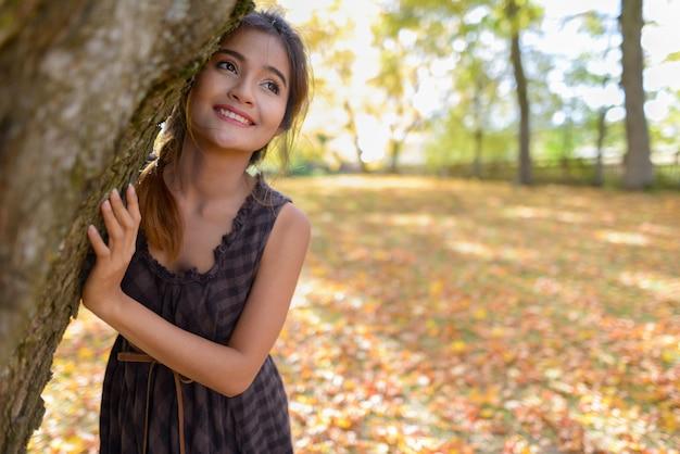 Jovem mulher asiática feliz sorrindo enquanto olha para cima divertidamente se escondendo atrás de uma árvore