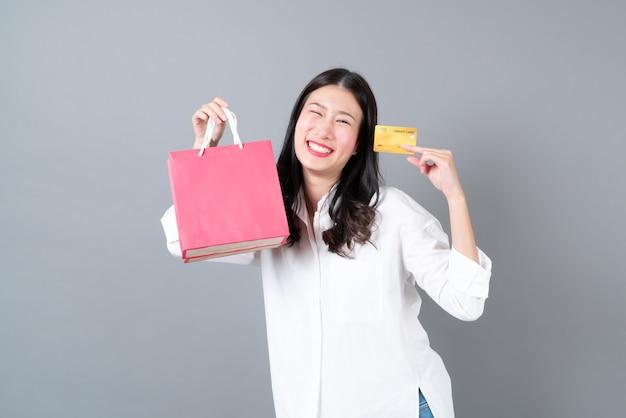 Jovem mulher asiática feliz sorrindo segurando um cartão de crédito e sacolas de compras