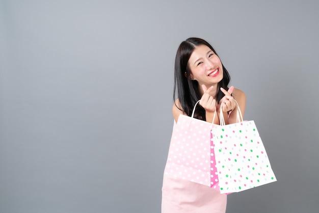 Jovem mulher asiática feliz sorrindo segurando uma sacola de compras em um vestido rosa cinza com espaço de cópia