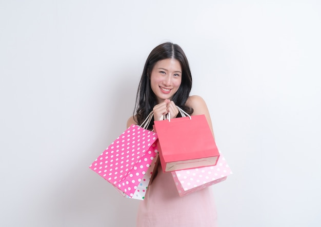 Jovem mulher asiática feliz sorrindo segurando uma sacola de compras em um vestido rosa com branco