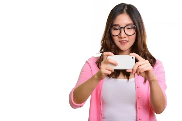 Jovem mulher asiática feliz tirando foto com o celular isolado contra o branco