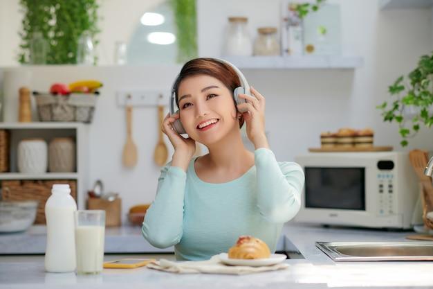 Jovem mulher asiática gosta de ouvir música com fones de ouvido e relaxar.