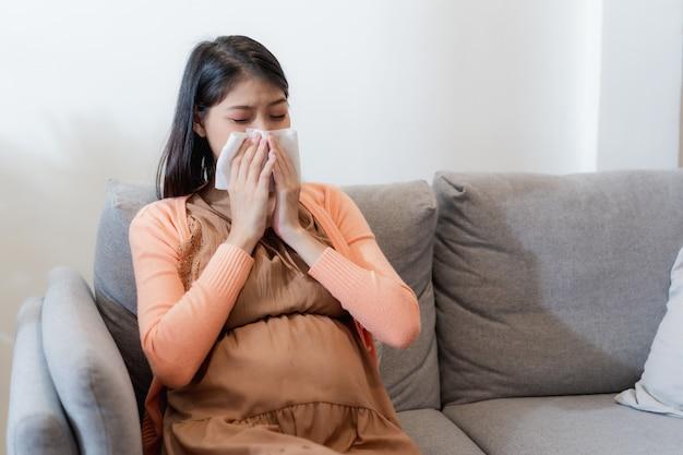 Jovem mulher asiática grávida sofre de gripe e espirros, coriza, nariz entupido