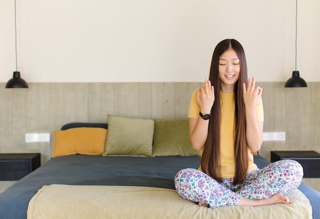 Jovem mulher asiática gritando agressivamente com olhar irritado, frustrado e irritado e punhos cerrados, sentindo-se furiosa