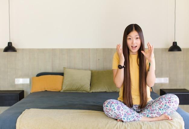 Jovem mulher asiática gritando com as mãos para cima, furiosa, frustrada, estressada e chateada