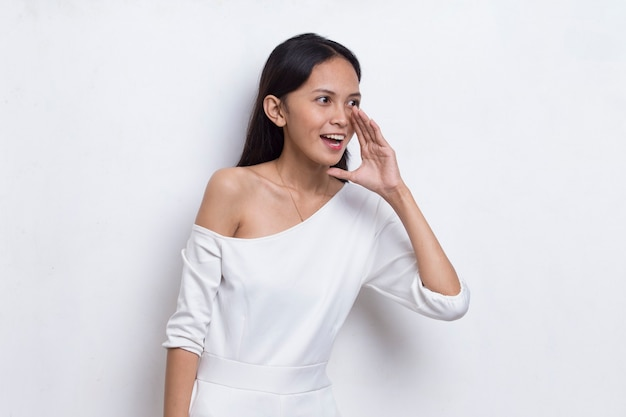 Jovem mulher asiática gritando e gritando, anunciando isolado no fundo branco