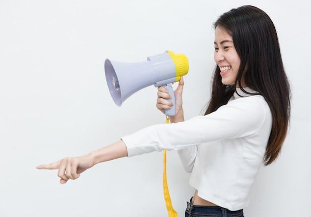Jovem mulher asiática gritando e gritando com o megafone em fundo branco, com espaço de cópia