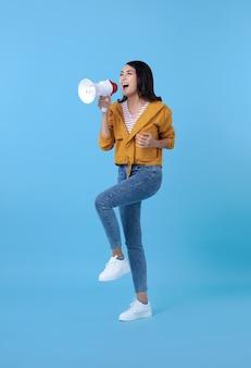 Jovem mulher asiática gritando no megafone, fazendo anúncio em azul.