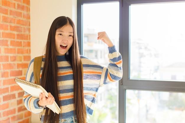 Jovem mulher asiática gritando triunfantemente, parecendo uma vencedora animada, feliz e surpresa, comemorando