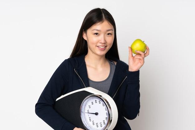 Jovem mulher asiática isolada com balança e uma maçã