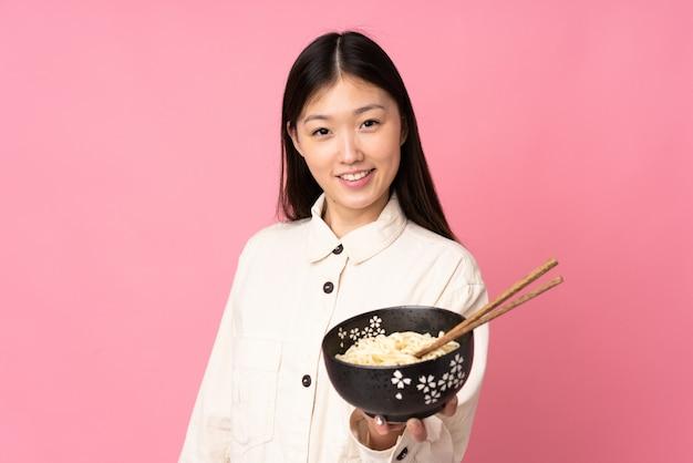 Jovem mulher asiática isolada em rosa com expressão feliz, mantendo uma tigela de macarrão com pauzinhos