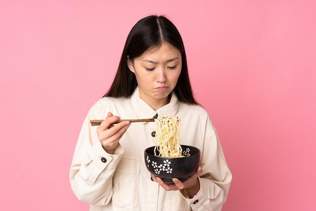 Jovem mulher asiática isolada em rosa, segurando uma tigela de macarrão com pauzinhos