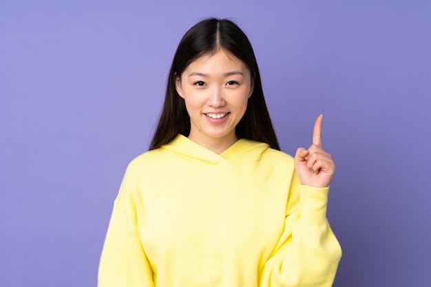 Jovem mulher asiática isolada em roxo, mostrando e levantando um dedo em sinal dos melhores