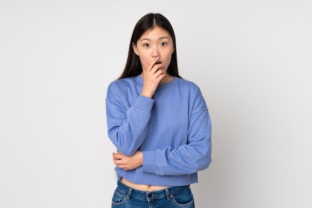 Jovem mulher asiática isolada em surpreso e chocado ao olhar para a direita