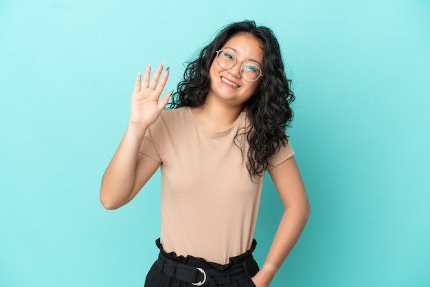 Jovem mulher asiática isolada em um fundo azul, saudando com a mão e com uma expressão feliz