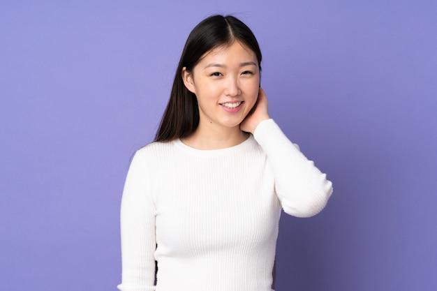 Jovem mulher asiática isolada na risada roxa
