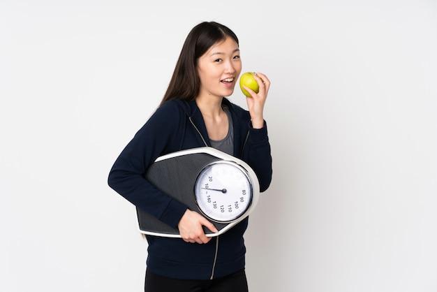 Jovem mulher asiática isolada no espaço em branco com máquina de pesagem e com uma maçã