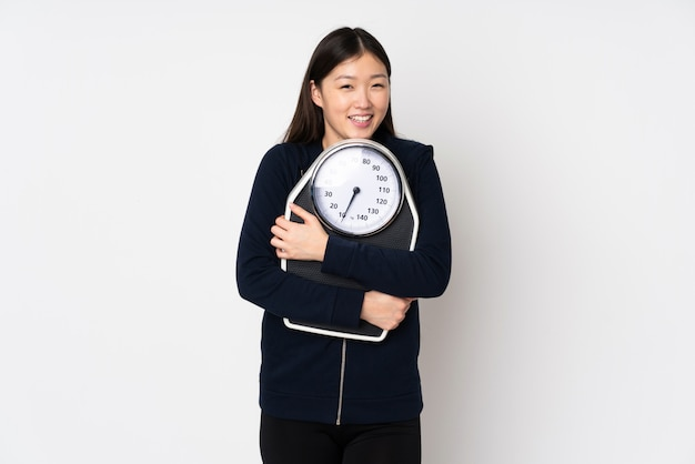 Jovem mulher asiática isolada no espaço em branco com máquina de pesagem