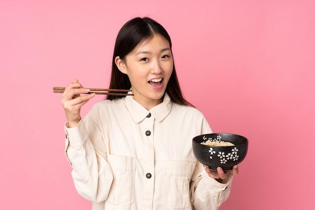Jovem mulher asiática isolada no espaço rosa, segurando uma tigela de macarrão com pauzinhos