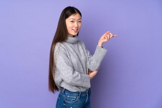 Jovem mulher asiática isolada no fundo apontando o dedo para o lado