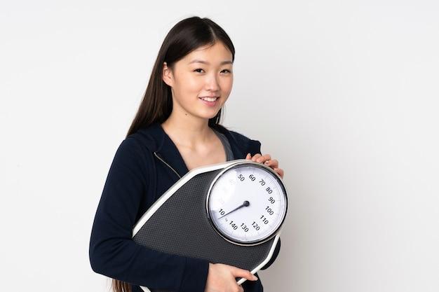 Jovem mulher asiática isolada no fundo branco com balança