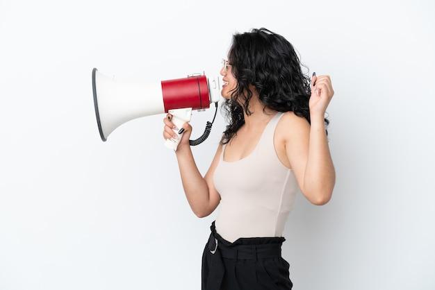 Jovem mulher asiática isolada no fundo branco gritando em um megafone para anunciar algo em posição lateral