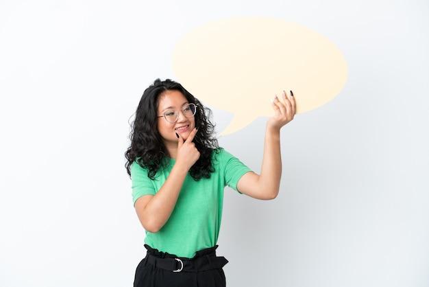 Jovem mulher asiática isolada no fundo branco segurando um balão de fala vazio e apontando-o