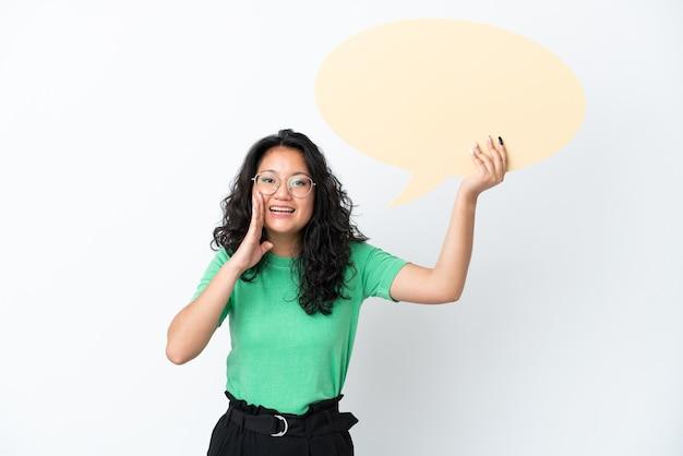 Jovem mulher asiática isolada no fundo branco segurando um balão de fala vazio e gritando