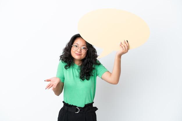 Jovem mulher asiática isolada no fundo branco segurando um balão de fala vazio e tendo dúvidas