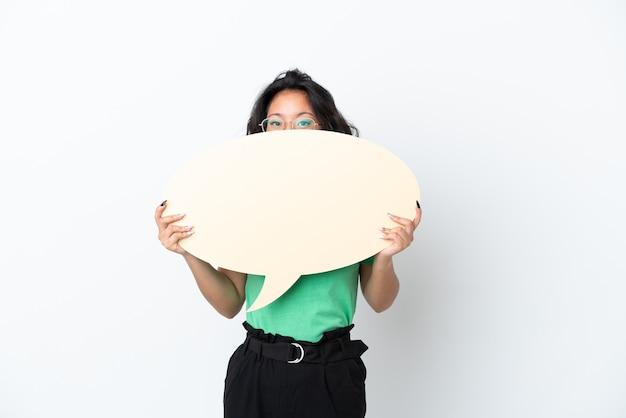 Jovem mulher asiática isolada no fundo branco segurando um balão de fala vazio escondido atrás dele.