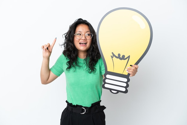 Jovem mulher asiática isolada no fundo branco segurando um ícone de lâmpada e pensando