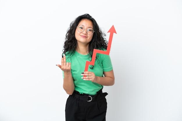 Jovem mulher asiática isolada no fundo branco segurando uma flecha ascendente e fazendo o gesto de aproximação