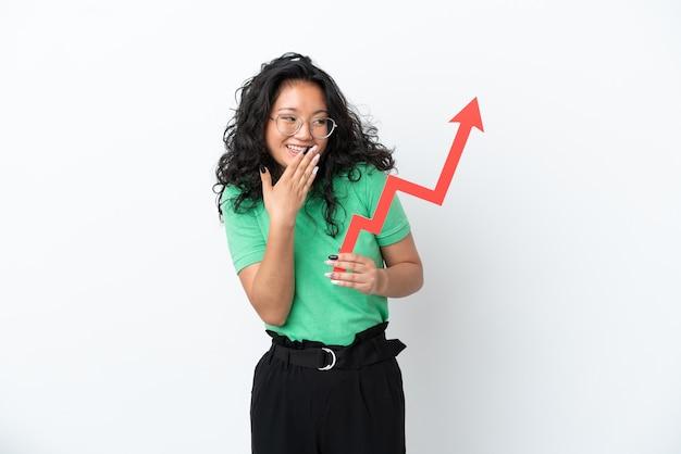 Jovem mulher asiática isolada no fundo branco segurando uma flecha em ascensão com expressão de surpresa