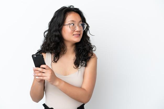 Jovem mulher asiática isolada no fundo branco usando telefone celular e olhando para cima