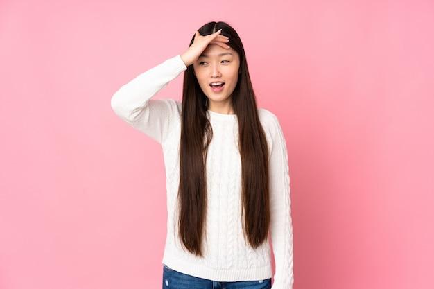 Jovem mulher asiática isolado fazendo gesto de surpresa enquanto olha para o lado