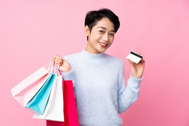 Jovem mulher asiática isolado parede rosa segurando sacolas de compras e um cartão de crédito