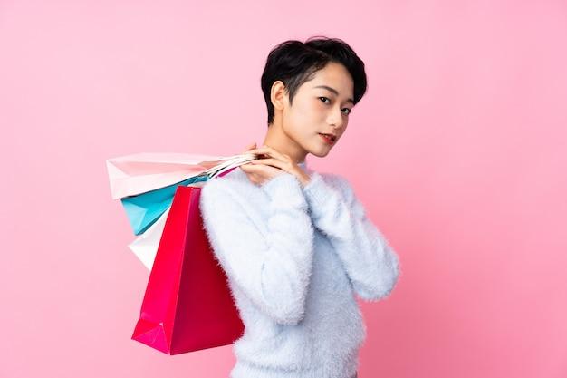 Jovem mulher asiática isolado parede rosa segurando sacolas de compras