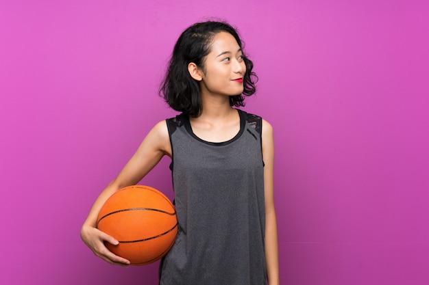 Jovem mulher asiática jogando basquete na parede roxa isolada