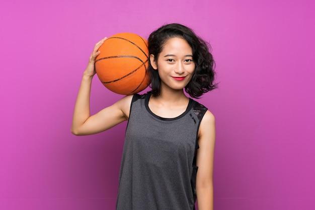 Jovem mulher asiática jogando basquete na parede roxa
