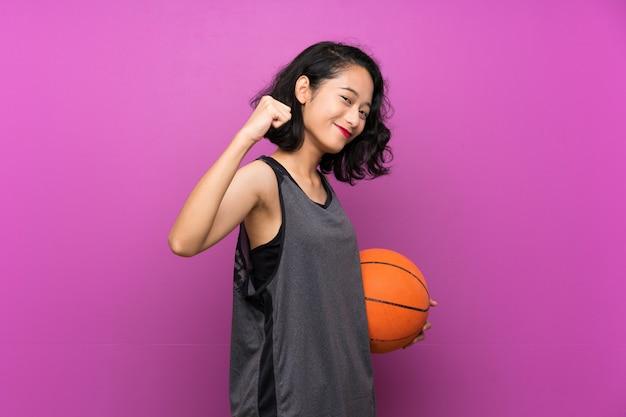 Jovem mulher asiática jogando basquete sobre fundo roxo isolado