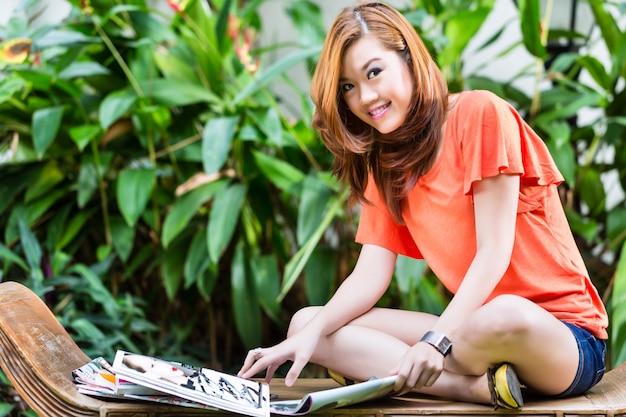 Jovem mulher asiática lendo revista de moda